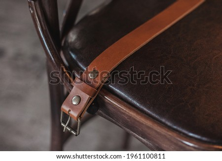 A handmade craft leather belt rests on the chair. Exclusive, Life style, horizontal orientation, no people, copy space Royalty-Free Stock Photo #1961100811