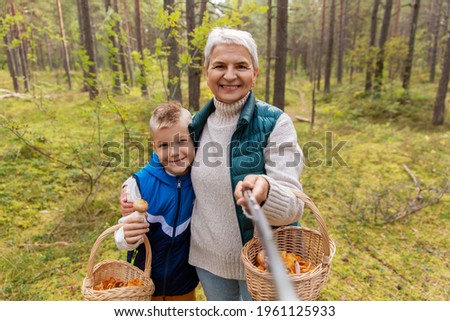 picking season, leisure and people concept - happy smiling grandmother and grandson with mushrooms in baskets taking picture with selfie stick in forest