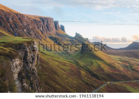 Golden light at sunset or sunrise over colourful landscape view of the rugged, otherworldly terrain of the Quiraing on the Isle of Skye, Scotland. Royalty-Free Stock Photo #1961138194