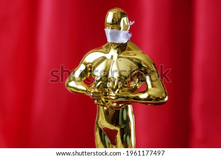 Hollywood Golden Oscar Academy award statue in medical mask on red curtains background. Success and victory concept. Oscar ceremony in coronavirus time