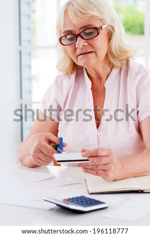 Cutting her budget. Concentrated senior woman cutting her credit card with scissors while sitting at the table #196118777