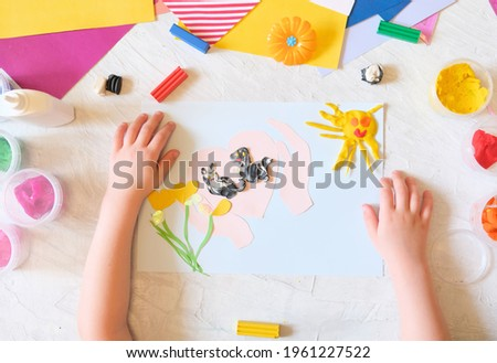 Child making card from colorful paper and plasticine. Card for International  Homeless Animals day. Pets adoption concept. Explain to the child through play and creativity about important things