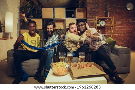 Sport party. Group of friends watching TV, sport match together. Emotional fans cheering for favourite team, watching football. Concept of friendship, leisure activity, emotions. Betting, finance, fun Royalty-Free Stock Photo #1961268283