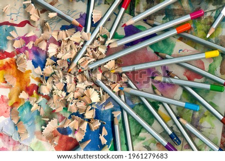 Set wooden color pencils. Wooden pencil shavings and colorful crumbs of graphite from sharpener on abstract background. Back to school wallpaper. Art time image.
