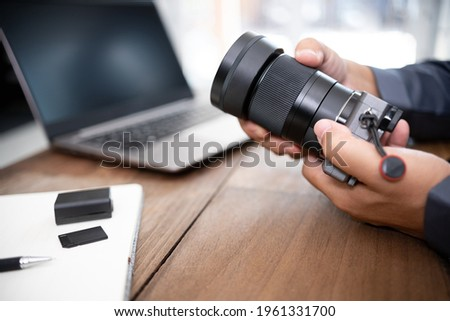 A man change camera lens and camera and photography equipment on table