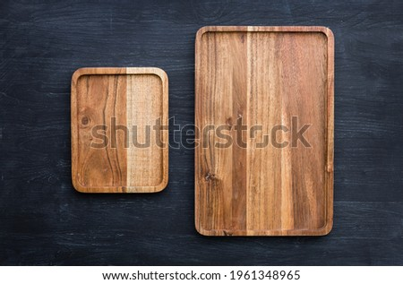 Mango tree wooden kitchen board. Perfect place to cut meat. Place for the dish. Beautiful painted dark navy blue background. Food advertising. Pictures of dishes in the restaurant. Wooden serving tray