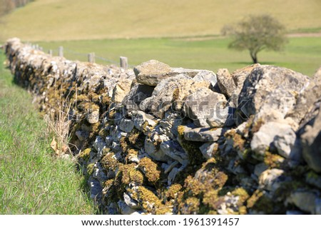 Close up details of old dry stone wall boundary covered with moss and lichen in Cotswold landscape Royalty-Free Stock Photo #1961391457