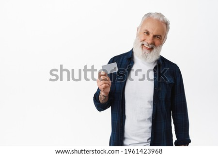 Smiling mature man with tattoos shows credit card, laughs and looks happy at camera, recommends bank, paying contactless, order with card, stands over white background