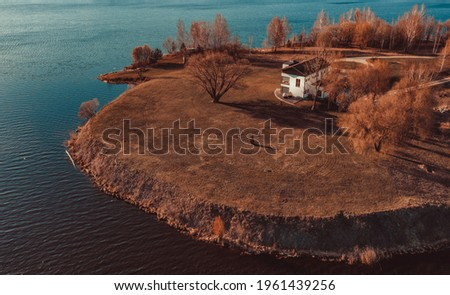View on red holiday cabin by a lake in Stockholm archipelago, Sweden. Wooden cottage, sauna on shore. Tiny house near the water. Rocky small island, islet in water. Buildings surrounded by green trees Royalty-Free Stock Photo #1961439256