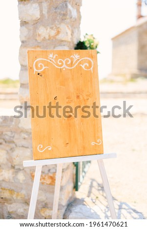 Blank wooden easel with monograms stands near a stone column on a stand