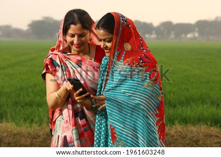 Indian rural women's looking phone in village  Royalty-Free Stock Photo #1961603248