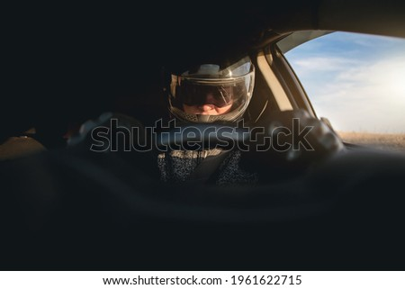 Rally racer in a helmet is driving a car concept. Royalty-Free Stock Photo #1961622715