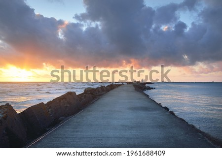 Old pier (walkway, promenade) to the lighthouse. Breakwaters close-up. Clear blue sky, pink sunset clouds, golden sunlight. Seascape, cloudscape. Baltic sea. Spring. Tourism, landmark, navigation Royalty-Free Stock Photo #1961688409