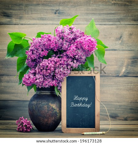 bouquet of lilac flowers on wooden background. blackboard with sample text Happy Birthday! retro style toned picture