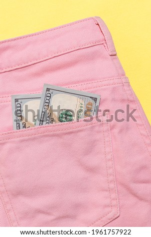 Two new banknotes of one hundreds dollars lying in back pockets of women's pink pants. Pink trousers on yellow backdrop.