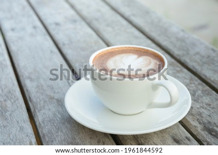A white coffee cup on top with a heart shaped milk froth placed on top of a stick and a space on top of the picture.