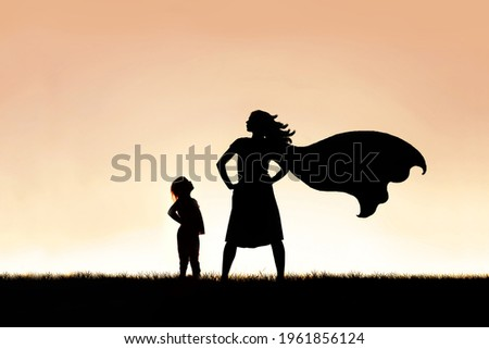 The silhouette of a strong, beautiful caped super hero woman stands isolated against a sunset in the sky background. Royalty-Free Stock Photo #1961856124