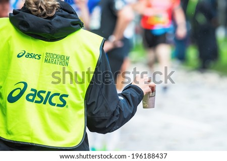 STOCKHOLM - MAY 31: Volunteer gives out mugs with water in a depot in the ASICS Stockholm Marathon 2014. May 31, 2014 in Stockholm, Sweden. #196188437