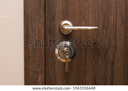 Door handle and lock with keys close-up. Closed modern entrance door in oak color. Royalty-Free Stock Photo #1961926648