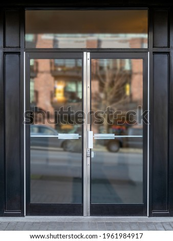 Exterior building entrance with black steel double glass door and defocused reflection from traffic and neighboring building. Commercial, business or residential lobby entrance. Selective focus.