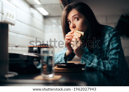 Hungry Woman Eating a Sandwich at Night in the Kitchen. Young person stress eating during nighttime having a late snack   Royalty-Free Stock Photo #1962027943