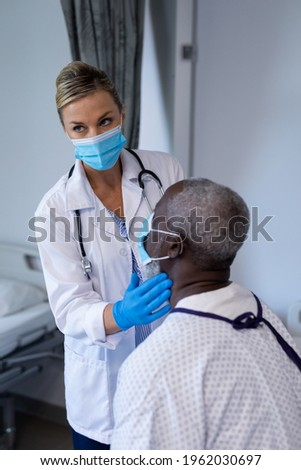 Caucasian female doctor wearing face mask palpating lymph nodes of african american male patient. medicine, health and healthcare services during coronavirus covid 19 pandemic. Royalty-Free Stock Photo #1962030697