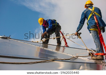 Male two workers rope access height safety connecting with a knot safety clipping into roof fall arrest and fall restraint anchor point systems ready to ascending, construction site oil tank dome. Royalty-Free Stock Photo #1962035440