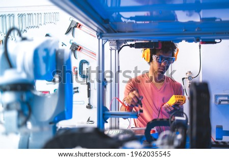 Male Engineers Maintenance Robot Arm at Lab. he are in a High Tech Research Laboratory with Modern Equipment. Technology and Innovation Concept. Royalty-Free Stock Photo #1962035545