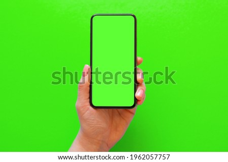 Person holding mobile phone with green screen on green background