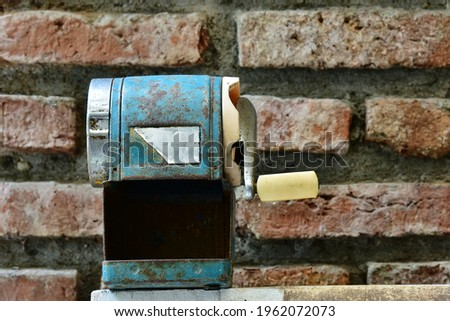 old pencil sharpener placed at the front of clay bricks wall look vintage style