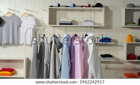Clothes at custom clothing printing company. Set of blank pastel cotton white, gray, blue and pink sportswear on a rail in the store. Web Banner