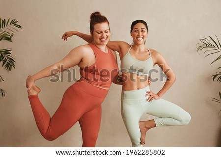 Women sportswear standing together on one leg at fitness studio. Females exercising at health club. Royalty-Free Stock Photo #1962285802