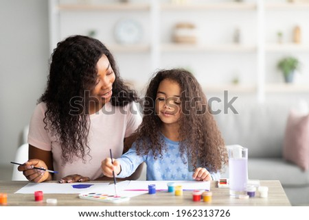 Portrait of happy black mother and her daughter painting with watercolors and gouache at home. Adorable little girl and her parent creating picture together, doing arts. Family hobbies concept