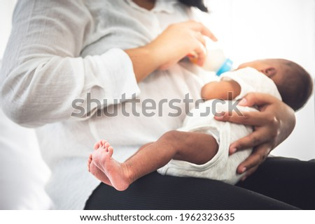 Blurred soft images of mother Sitting on bed, and feed milk from bottle milk to her 12-day-old African baby black skin newborn son, This picture focused on foot baby, to family and food infant concept