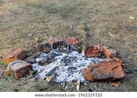 Gray ashes in abandoned fire place red bricks ring on grass close up, outdoors picnic leisure, empty campsite fireplace safety on a spring day, picture with copy space