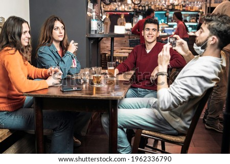 Group of young people having fun drinking beers at the cafe. Friends taking smartphone video and pictures sitting at the pub's table Young people behaviors in the new normal during coronavirus.
