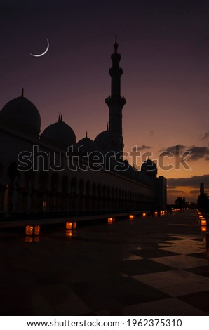 A silhouette of a mosque against dimly lit sky with Eid crescent. Islamic Eid or Ramadan background. Royalty-Free Stock Photo #1962375310