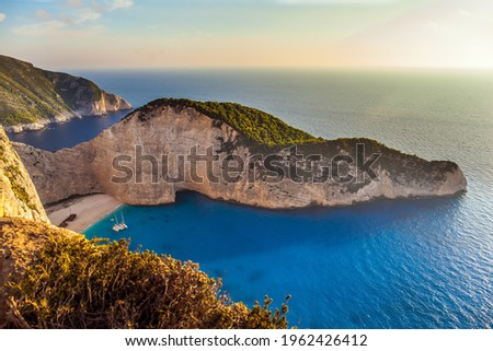 The magical island of Zakynthos on the Mediterranean. The cove with a small sandy beach. The sky glows a warm sunset. Summer holidays in Greece. The concept of a summer beach holiday and photo tourism