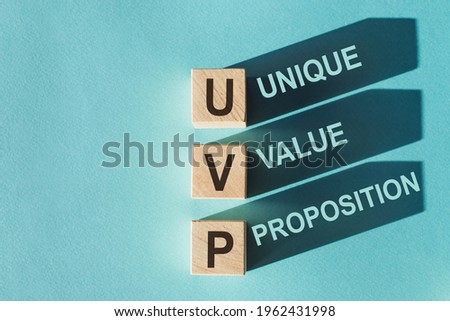 Wooden cubes building word UVP - (abbreviation Unique Value Proposition) on light blue background.