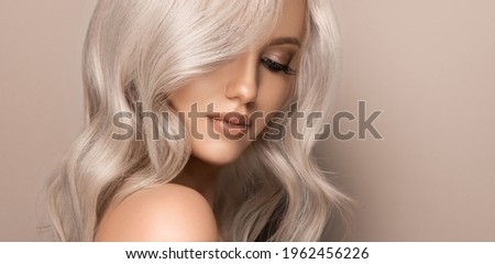Beautiful girl with hair coloring in ultra blond. Stylish hairstyle curls done in a beauty salon. Fashion, cosmetics and makeup Royalty-Free Stock Photo #1962456226