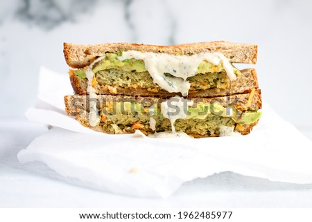 Vegan Ranch Dressing drizzled in a veggie burger sandwich - white background - straight on Royalty-Free Stock Photo #1962485977