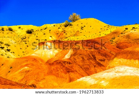 Sand hill in the middle of the desert. Orange yellow sand hill on clear blue sky background. Sand hill on blue sky background. Sand hill view Royalty-Free Stock Photo #1962713833