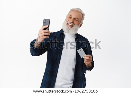 Happy senior man taking selfie with his credit card, smiling as paying online with face id on smartphone app, shopping in internet shop, standing against white background