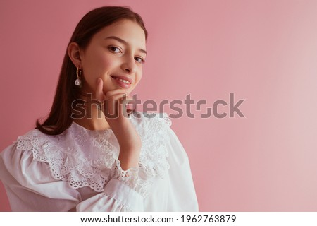 Elegant brunette woman wearing stylish pearl earrings, white cotton blouse with vintage lace collar. Copy, empty space for text