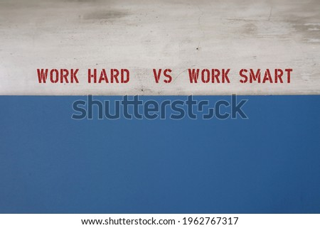 Blue copy space background and grey wall with text WORK HARD VS WORK SMART,  smart worker complete work within timelines using shortcut ,proper planning , prior research , instead of working long hour Royalty-Free Stock Photo #1962767317