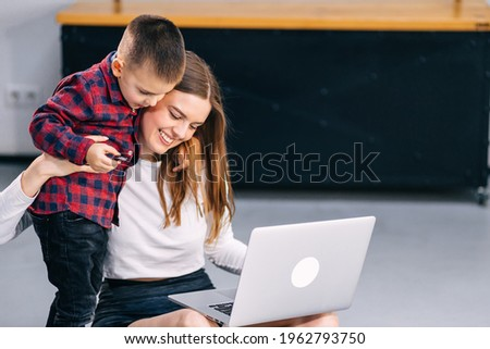 cheerful mom turns on cartoons on the laptop to her son while she does yoga.