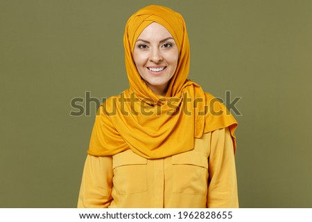 Smiling happy fun young arabian asian muslim woman 20s in abaya hijab yellow clothes isolated on olive green khaki color background studio portrait. People uae middle eastern islam religious concept Royalty-Free Stock Photo #1962828655