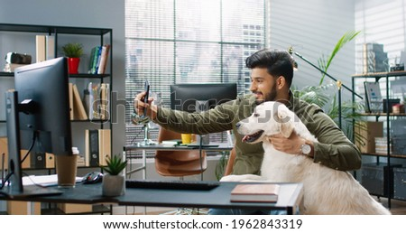 Happy joyful Hindu male sitting in cabinet at work making selfie photo with his cute dog pet in good mood. Handsome cheerful bearded guy at office taking pictures with animal on smartphone camera
