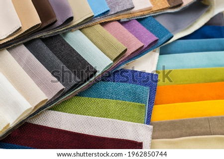 Samples of fabrics for upholstery, roman blinds. Multicolored fabric swatches spread out in a circle. Royalty-Free Stock Photo #1962850744