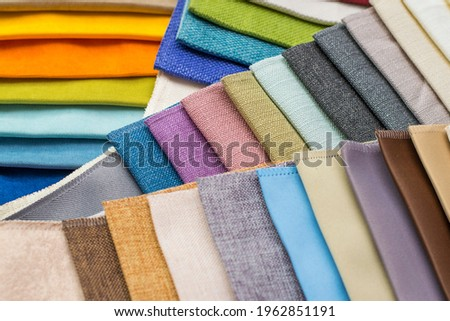 Samples of fabrics for upholstery, roman blinds. Multicolored fabric swatches close up Royalty-Free Stock Photo #1962851191